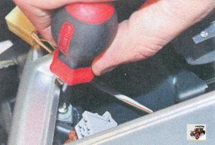 винты крепления накладки консоли, расположенные по бокам окна под автомагнитолу