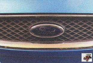 замок капота находится под эмблемой автомобиля на решетке радиатора