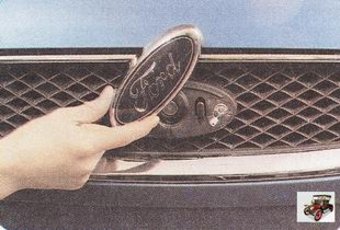эмблема замка капота на решетке радиатора