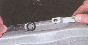 удерживая шток от вращения отворачиваем гайку верхнего крепления амортизатора