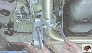 гайки двух стяжных болтов хомута крепления трубы основного глушителя к трубе дополнительного глушителя