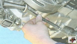 выпрессуйте обойму сальника штока из картера коробки передач