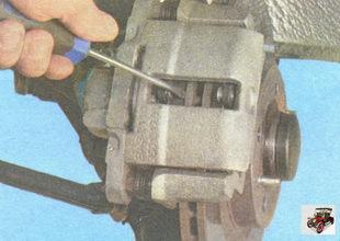 вставив большую отвертку между внутренней тормозной колодкой и тормозным диском
