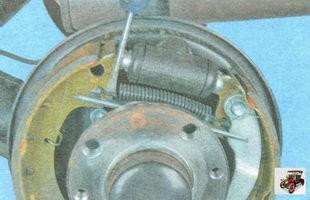 снимите верхнюю стяжную пружину задних тормозных колодок