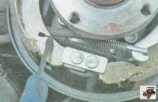 снимите нижнюю стяжную пружину задних тормозных колодок