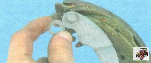 снимите опорную шайбу с пальца разжимного рычага задней тормозной колодки
