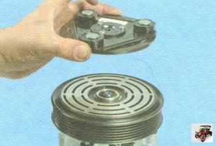 снимите прижимную пластину с вала компрессора кондиционера