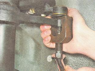 съемником выпрессовываем шаровой палец из отверстия поворотного кулака