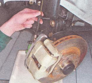извлекаем тормозной шланг из кронштейна на стойке передней подвески