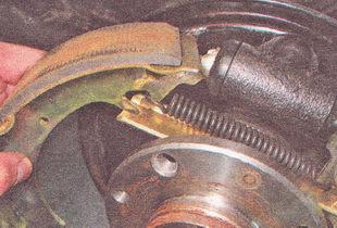 отводим нижнюю часть передней тормозной колодки