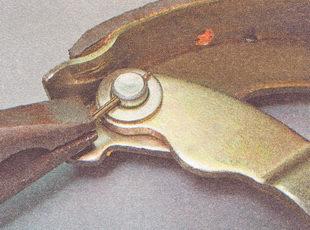 снимаем с тормозной колодки шайбу, распорный рычаг и осевой палец