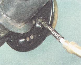 выводим трос ручного тормоза из отверстия опорного щита заднего тормозного механизма