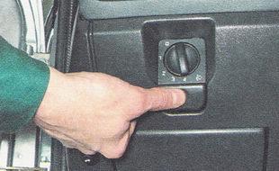 нажав кнопку, находящуюся под рукояткой управления гидрокорректором фар, открываем крышку монтажного блока