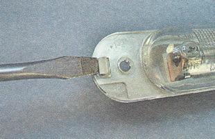 фиксатор рассеивателя фонаря освещения номерного знака и снимаем рассеиватель