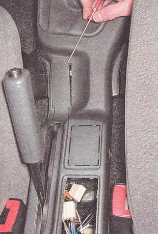 отжимаем фиксаторы рамки рычага стояночного тормоза