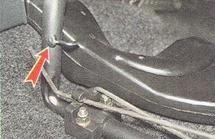 выводим конец верхнего торсиона из зацепления с передней стойкой сиденья
