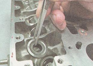 пинцетом снимаем тарелку пружины клапана
