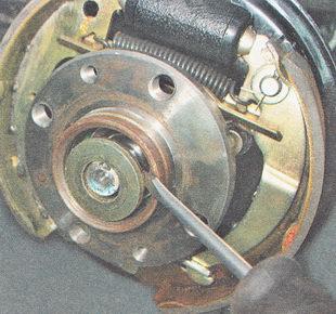 снимаем гайку и упорную шайбу гайки ступицы заднего колеса