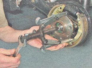 съемником спрессовываем ступицу с оси вместе с подшипником