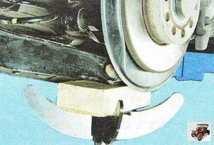 установите под задний поперечный рычаг подвески опору и опустите автомобиль