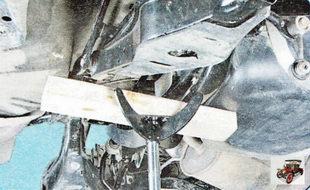установите под поперечину задней подвески гидравлические стойки или домкраты