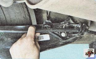 вытяните трос стояночного тормоза из держателя на рычаге задней подвески
