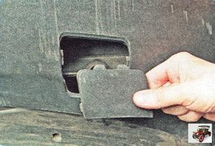 снимите крышку, закрывающую отверстие под буксировочную проушину преодолевая усилие фиксаторов