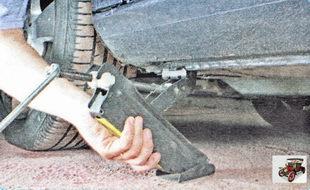 Установите домкрат под автомобиль рядом с колесом, которое нужно заменить