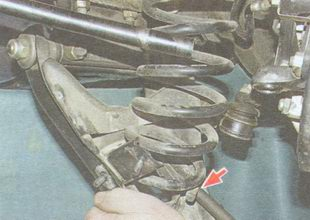 выведите нижний конец пружины передней подвески из нижней опорной чашки